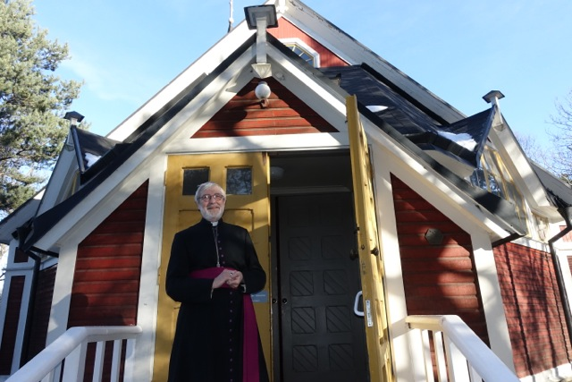 präst framför kyrka