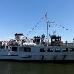En båt kommer lastad med nybakade studenter