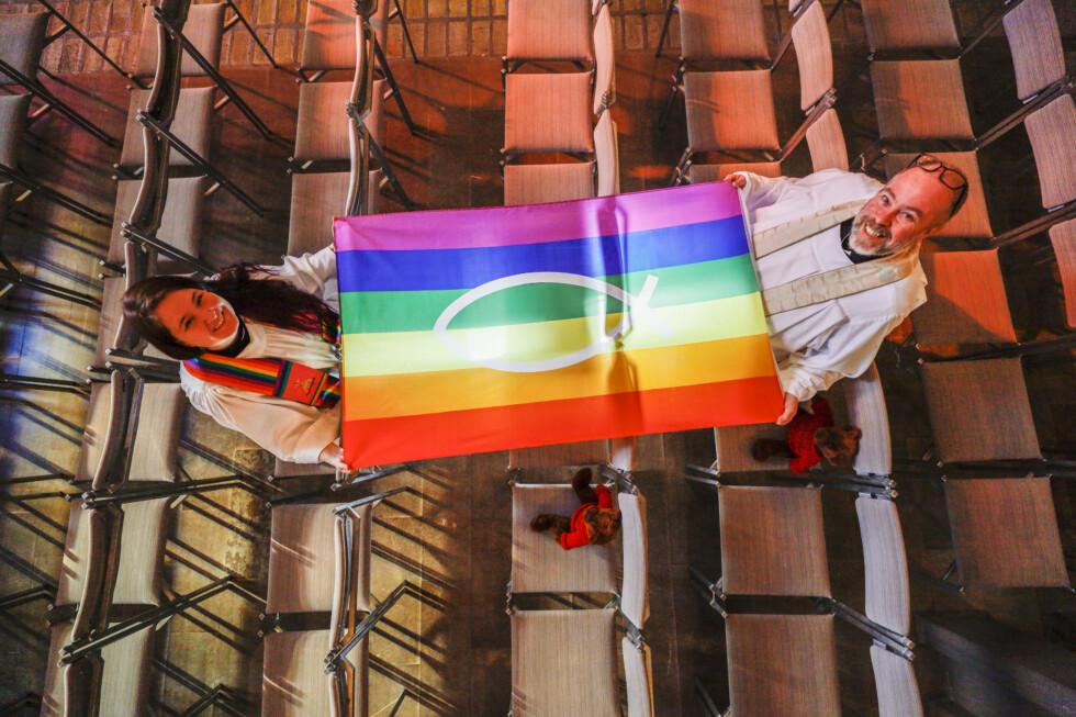 två präster håller i en regnbågsflagga