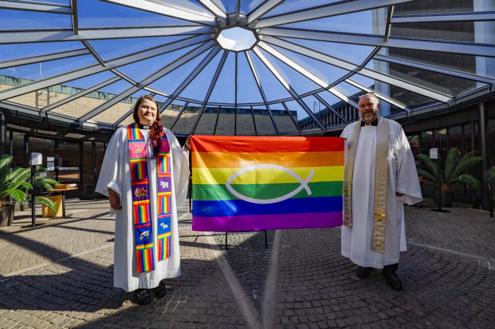 två präster håller regnbågsflagga