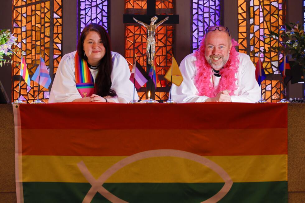 Två präster och Prideflaggan i en kyrka