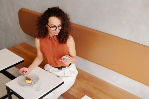 kvinna på cafe videochattar med sin mobil